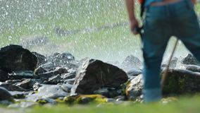 An underground fountain coming between the rocks on the ground. A man on a foreground probes the ground with a stick. Mid shot stock video