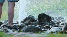 An underground fountain coming between the rocks on the ground. Mid shot stock video footage