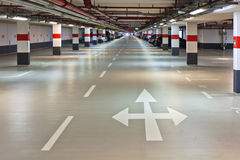 Underground garage. View of a underground garage with arrow markings and headlights of a car at the vanishing point Stock Photography