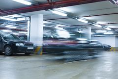 Underground garage. The shined underground garage with the moving cars and parked cars Royalty Free Stock Photography