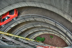 Underground Garage. Downward view of a circular concrete ramp leading to an underground garage.  A car in movement can be seen on the first level of the ramp Stock Photos