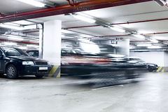 Underground garage. The shined underground garage with the moving cars and parked cars Royalty Free Stock Photo