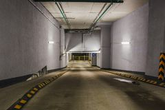 Underground garage or modern car parking. Entry or descent down to Underground garage or modern car parking, concrete tunnel or corridor, perspective Royalty Free Stock Photography