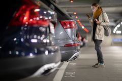 Underground garage or modern car parking. With lots of vehicles, perspective of the row of the cars with a female driver looking for her vehicle royalty free stock photos