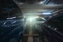 Underground garage or modern car parking with lots of vehicles. Toned royalty free stock image