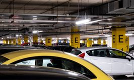 Underground garage in a shopping mall with a lot of cars. And a visible air conditioning system Royalty Free Stock Images