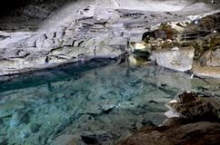 Underground lake in the Ice Cave in Kungur. Russia. Underground river with the purest clear blue water and rocky bottom next to tourist path, enclosed by royalty free stock photography