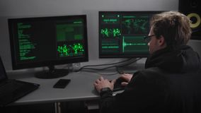 The underground organization. The hacker tries to break into critical information. On two computers and a laptop desk. On the wall board with information and a stock video
