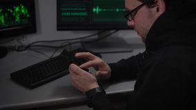 The underground organization. Two computers and a laptop on desk. A man in a dark jacket and glasses looks at the stock video