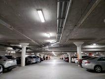Underground parking garage. Underground pablic parking garage with cars parked on both sides of the isle Stock Photo