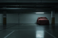 Underground parking background. Red covered vintage car in empty underground parking background with copy space Stock Photo
