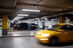 Underground parking garage in a shopping mall. With a quickly driving yellow car Stock Image
