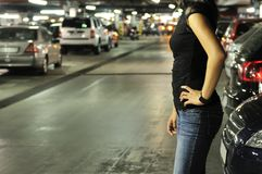 Underground parking place story. Young woman standing at car in underground parking place Stock Image