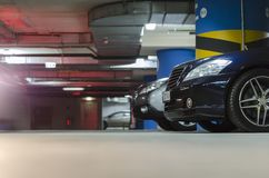 Underground parking. Side of red car on the underground parking Royalty Free Stock Photo
