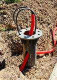 An underground part of a flange bearing of a light pole with power cables Royalty Free Stock Photo