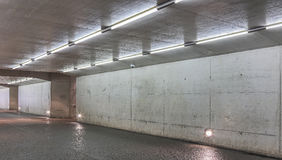 Underground passage. An underground passage with concrete walls and ceiling lit by fluorescent lamps Stock Image