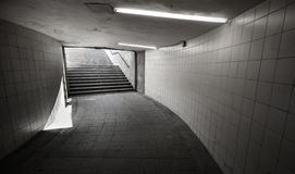 Underground passage with lights and stairs. In the glowing end Royalty Free Stock Image