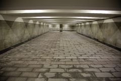 Long underground passage. The underground passage lined with gray granite and marble Royalty Free Stock Photos
