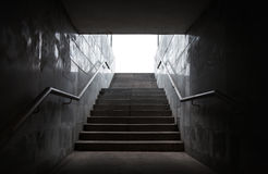 Underground passage with stairs. In the glowing end Royalty Free Stock Photography