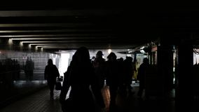 Underground pedestrian crossing, an anonymous crowd of people goes to the side or from the underground subway steps. Silhouettes of people in the underground stock footage
