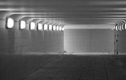 Underground pedestrian passage. Black and white view of tiled underground pedestrian passage with light shining through windows Royalty Free Stock Photos
