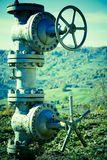 Underground Pipeline Valves. Closeup view of piping and valves that protrude above ground in a rural, hilly countryside and are connected to an underground Stock Photo