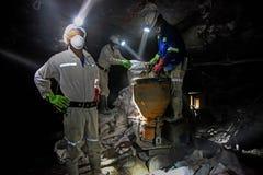 Underground Platinum Chrome miners mixing cement stock photo