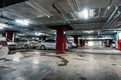 Underground public garage parking with cars. Movie style toned stock photos