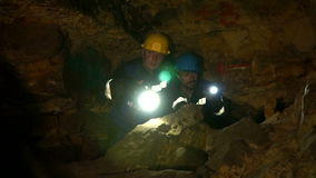 Underground researchers climb in an underground tunnel. Lighting lanterns new place. stock video