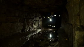 Underground researchers climb in an underground tunnel. Passage through the puddle. Underground researchers climb in an underground tunnel. Abandoned quarries stock video