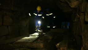 Underground researchers climb in an underground tunnel. Passage by road signs. Underground researchers climb in an underground tunnel. Abandoned quarries under stock footage