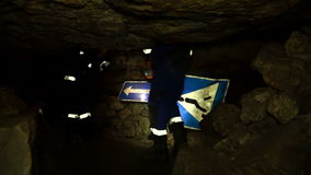 Underground researchers climb in an underground tunnel. Passage by road signs. Underground researchers climb in an underground tunnel. Abandoned quarries under stock video footage