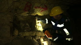 Underground researchers climb in an underground tunnel. Passing by the stone heads. Underground researchers climb in an underground tunnel. Abandoned quarries stock video footage