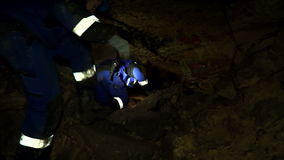 Underground researchers climb in an underground tunnel. Passing through the stones blockage. stock video