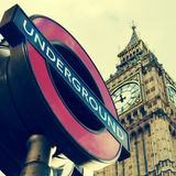 Underground sign and the Big Ben in London, United Kingdom, with. A view of a typical underground sign and the Big Ben in the background, in London, United Stock Image