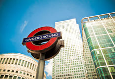 Underground sign, Canary Wharf, London. Close-up on Underground sign in Canary Wharf, Docklands, London. One Canada Square in the background on the right Royalty Free Stock Image