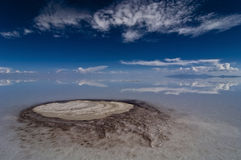 Underground spring penetrates through salt crus. Underground spring penetrates through up to ten meters salt crust bringing minerals to surface at salar de uyuni Royalty Free Stock Images