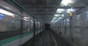 Underground train arriving to the station. Subway train moving in the dark tunnel and arriving to the station, oncoming train leaving. View from the train cabin stock footage