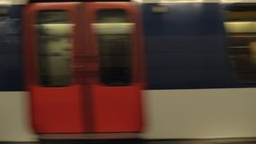 Subway train leaving underground station. Underground train leaving the station and gathering speed, carriages passing by stock footage
