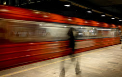 Underground train in Oslo. Underground T-bane train in Oslo< norway seen in slow motion blur with figure of person on platform in foreground royalty free stock photos