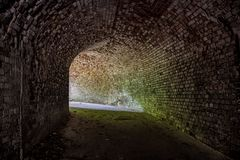 Underground vaulted red brick tunnel under abandoned German fortress. Turn the tunnel.  Stock Image
