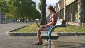 Underground and a young woman with a laptop. Girl with laptop on a bench painted street art stock footage
