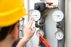 Underhåll - tekniker som kontrollerar uppvärmningtryckmeter Royaltyfri Foto