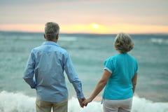 Underhållande åldringpar på en strand Arkivbilder