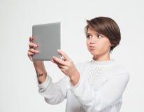 Underhållande kvinna som gör den roliga framsidan och tar selfie med minnestavlan Royaltyfri Fotografi