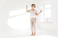 Underhållande kvinna som lyssnar till musik från mobiltelefonen och att dansa royaltyfri bild