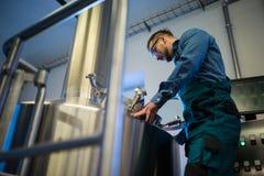 Underhållsarbetare som arbetar på bryggeriet royaltyfri bild