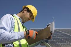 Underhållsarbetare som ser skrivplattan nära solpaneler royaltyfri fotografi
