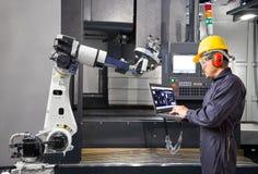 Underhållstekniker som använder den automatiska robotic handen för bärbar datordatorkontroll med CNC-maskinen i smart fabrik indu royaltyfri foto