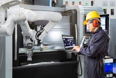 Underhållstekniker som använder den automatiska robotic handen för bärbar datordatorkontroll med CNC-maskinen i smart fabrik indu arkivfoto